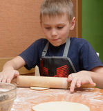 Massa nova do rolamento do menino com um grande pino do rolo de madeira como prepara os bolos Imagens de Stock