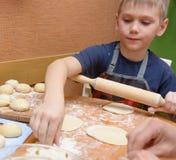 Massa nova do rolamento do menino com um grande pino do rolo de madeira como prepara os bolos Foto de Stock