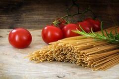 Massa orgânica do wholemeal, espaguetes secados, tomate e alecrins ele Fotografia de Stock