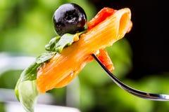 Massa Penne com azeitona preta bolonhesa do molho, do queijo parmesão do tomate e manjericão em uma forquilha Alimento mediterrân imagem de stock