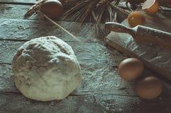 Massa, pino do rolo e orelhas do trigo no fundo de madeira floured Imagem de Stock