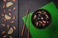 Massa preta do Fettuccine da tinta do calamar com camarões ou camarões, salsa, pimentão no vinho e molho da manteiga Vista superi imagem de stock