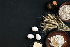 Massa que cozinha ingredientes na mesa de cozinha preta Vista superior com espaço para seu texto Fotos de Stock Royalty Free