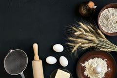 Massa que cozinha ingredientes na mesa de cozinha preta Vista superior com espaço para seu texto Fotos de Stock