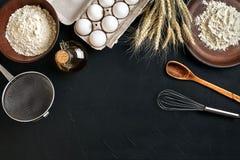 Massa que cozinha ingredientes na mesa de cozinha preta Vista superior com espaço para seu texto Imagem de Stock