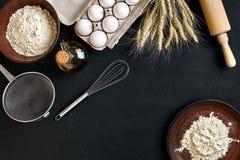 Massa que cozinha ingredientes na mesa de cozinha preta Vista superior com espaço para seu texto Foto de Stock