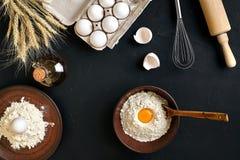 Massa que cozinha ingredientes na mesa de cozinha preta Vista superior com espaço para seu texto Foto de Stock Royalty Free
