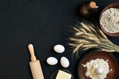 Massa que cozinha ingredientes na mesa de cozinha preta Vista superior com espaço para seu texto Fotografia de Stock
