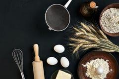 Massa que cozinha ingredientes na mesa de cozinha preta Vista superior com espaço para seu texto Fotografia de Stock Royalty Free