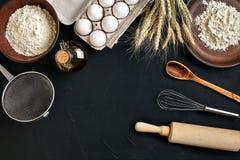 Massa que cozinha ingredientes na mesa de cozinha preta Vista superior com espaço para seu texto Imagem de Stock Royalty Free