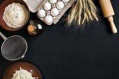 Massa que cozinha ingredientes na mesa de cozinha preta Vista superior com espaço para seu texto Imagens de Stock
