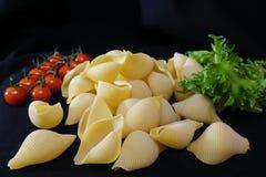 Massa sob a forma dos escudos em uma bacia de madeira redonda com tomates de cereja em um fundo preto Fundo culinário foto de stock