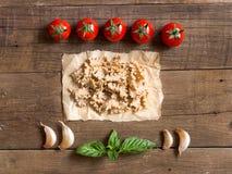 Massa, tomates, alho e manjericão no fundo de madeira foto de stock royalty free
