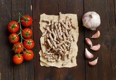 Massa, tomates e alho inteiros do trigo Imagem de Stock