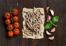 Massa, tomates, manjericão e alho inteiros do trigo Foto de Stock