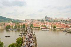 Massa van toeristen die op Charles-brug lopen stock foto