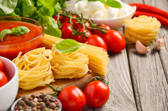 Massa, vegetais, ervas e especiarias para o alimento italiano na tabela de madeira rústica imagem de stock