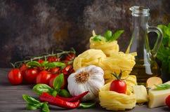 Massa, vegetais, ervas e especiarias para o alimento italiano no fundo de madeira imagem de stock