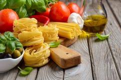 Massa, vegetais, ervas e especiarias para o alimento italiano no fundo de madeira branco foto de stock
