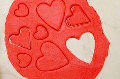 Massa vermelha com corações cinzelados de tamanhos diferentes em uma tabela branca Vista superior Imagem de Stock