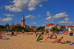 Massabezoekers die op Sopot-Strand, het Noorden zonnebaden van Polen met de Oude Vuurtoren op de achtergrond royalty-vrije stock foto's