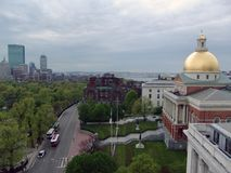 Massachusetts  State House in Boston on Beacon Street. Showing Beacon street and the Massachusetts State House on a cloudy day, to the left is the skyline and Stock Photos