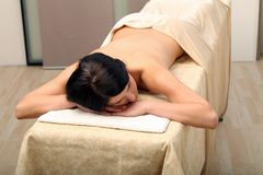 Massage. Brunette woman laying on a massage table stock image