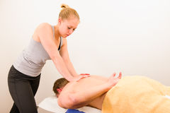 Massage. Professional masseur doing massage of male back Stock Images