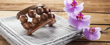 Massage accessory and orchid flowers on wood background for relaxation Royalty Free Stock Photo