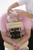 MASSAGE AMMA man receiving massage into a massage chair Royalty Free Stock Photography