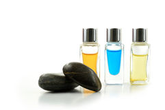 Massage Aromatherapy Oils. Studio macro of various bottled aromatherapy oils with stones against a white background. Copy space royalty free stock photos