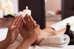 Massage av den mänskliga foten i brunnsortsalongen - mjuk fokus Arkivbild