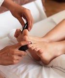 Massage av den mänskliga foten i brunnsortsalongen - mjuk fokus Royaltyfri Bild