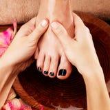 Massage av kvinnas fot i brunnsortsalong Arkivbild