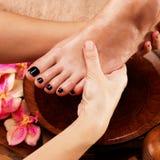 Massage av kvinnas fot i brunnsortsalong Royaltyfri Foto