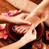 Massage av kvinnas fot i brunnsortsalong Royaltyfri Fotografi