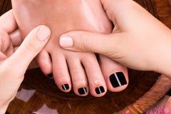 Massage av kvinnas fot i brunnsortsalong Arkivfoto