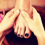 Massage av kvinnas fot i brunnsortsalong Royaltyfria Bilder