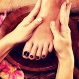 Massage av kvinnas fot i brunnsortsalong Royaltyfri Bild
