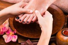 Massage av kvinnas fot i brunnsortsalong Arkivbilder