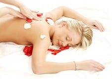 Massage avec des pétales de fleur images libres de droits