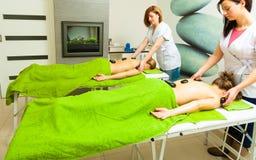 Massage avec les pierres chaudes de roches dans l'esthéticien image stock