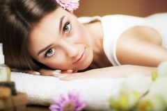 Massage. Beautiful woman at the spa. Gentle look. Flowers in hair. The concept of health and beauty. Dark background. Spa salon. Royalty Free Stock Photo
