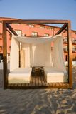 Massage Cabana on Beach. Wood framed cabana deck on sandy beach area.  Cabana appears to be for massage or relaxation, with canopied lounge seating and the Royalty Free Stock Photos