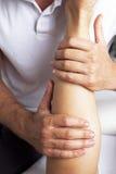 Massage calf muscle of a woman Stock Photos