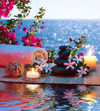 Massage with candles and tiare and Bougainvillea. Two candles and towels black stones and tiare - Bougainvillea on water royalty free stock image