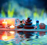 Massage with candles and tiare. Two candles and towels black stones and tiare on water royalty free stock photography