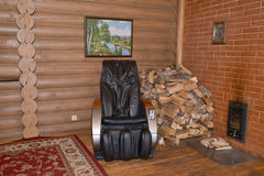 Massage chair and woodpile of firewood in a sauna Stock Photography