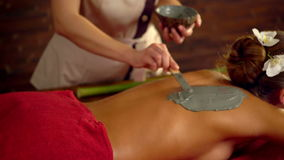 Massage and clay body mask in spa salon. stock video