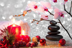 Massage composition christmas spa with candles, orchids and black stones. Glitter Stock Image